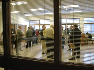 A group socializing in the multi-purpose room prior to the first presentation.